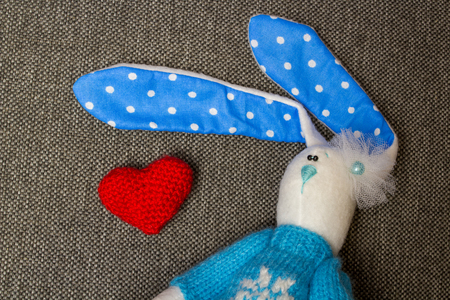 soft textile: Bunny With Heart. Macro Soft Toy at textile backgroung. Stock Photo