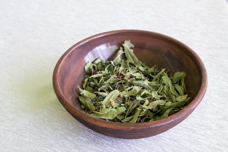 herbalism: Herbalism, Healing. Dried Herbs in a Clay Bowl at Blurred Background. Stock Photo