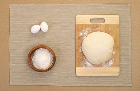 make a paste: bake ingredients: knead dough on wooden board and eggs, powder laying on table