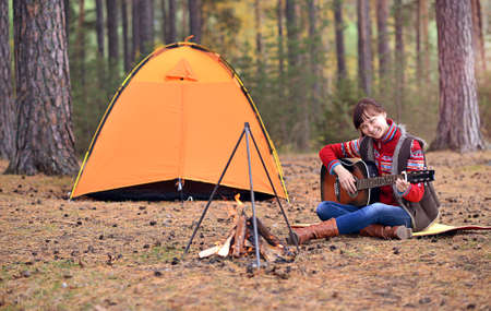 outumn: Young smiling girl playing guitar against tent at forest near fire Stock Photo