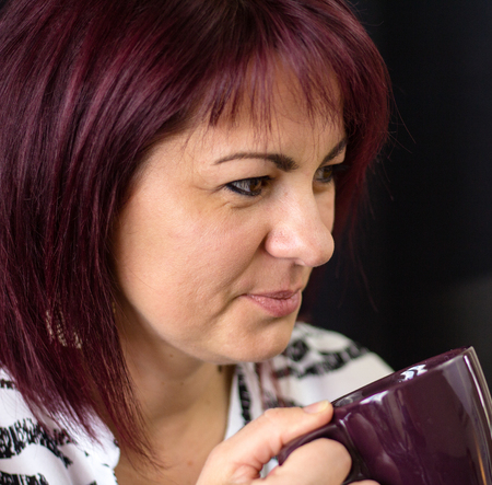 A red haared woman has a coffee break