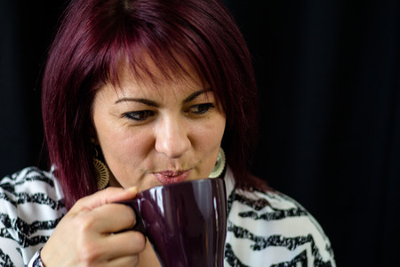 Red haared woman is holding a hot drink