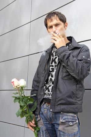 llegar tarde: Pretty chico posee tres rosas en una mano, fuma, busca en la c�mara y espera a la chica que es tarde  Foto de archivo