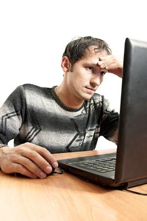 sadly: uomo stanco si siede ad un tavolo e purtroppo, guarda lo schermo portatile dopo aver preso una mano in testa Archivio Fotografico