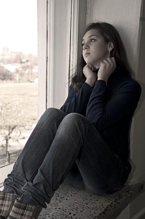 mujeres tristes: ni�a triste en la depresi�n se sienta en un alf�izar de ventana  Foto de archivo