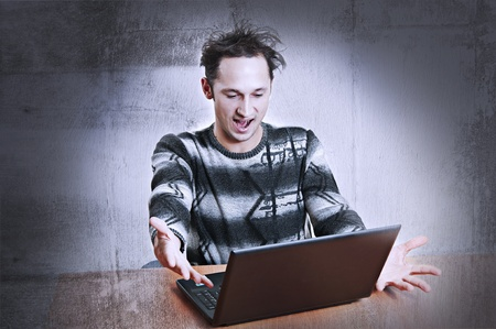 Adorably Shocked young adult man sit at table looks to laptop computer screen, opened a mouth. Obviously surprised by something.