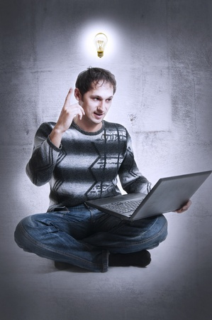 man - Programmer or freelancer with light bulb over head and laptop computer, lifted finger upwards (pointing). He found an ingenious decision of internet problem Stock Photo