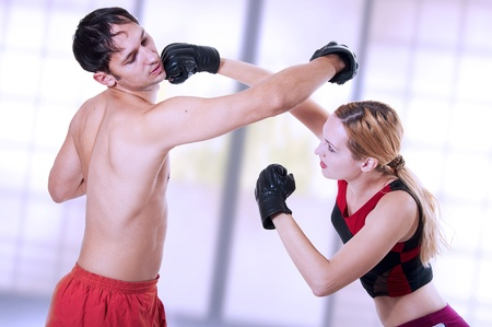 martial art. Female punching kicking man In jaw also she evaded from his attack.  kickboxing; cardio boxing; muay thai; taekwondo; Jiu-jitsu or mma. Couple fighters workout photo
