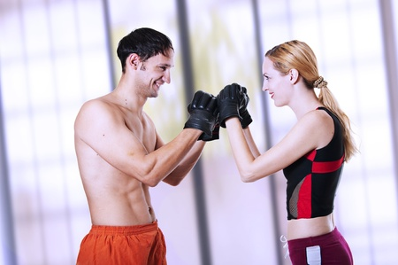 Man and woman fighters look against each other, having pressed fists in gloves - greet before the fight beginning. kickboxing; cardio boxing; muay thai; taekwondo; Jiu-jitsu; kungfu or mma. martial art. photo