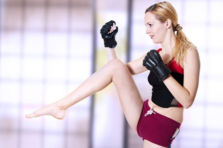 Young sexual lady fighter kicking leg front. Martial art - kickboxing; boxing; muay thai; taekwondo; Jiu-jitsu; kungfu or mma. Fight. photo