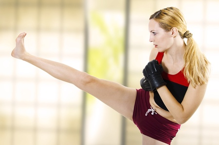 Young sexual woman fighter kick leg side. Fight. Martial art training - kickboxing; muay thai; taekwondo; Jiu-jitsu; kungfu or mma.