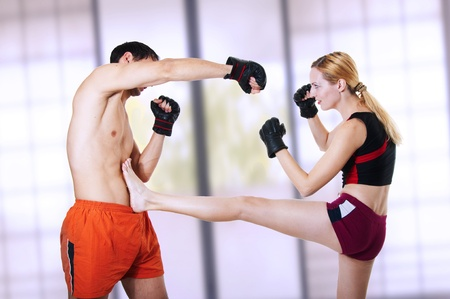 female boxing: young pretty sexual girl is protected from attack of man - front leg kiking in stomach. Martial art - kickboxing; cardio boxing; muay thai; taekwondo; Jiu-jitsu; kungfu or mma