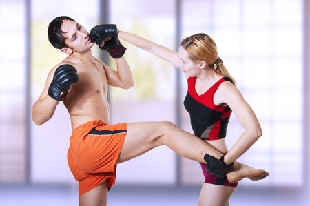 Couple fighters. Woman kicking. Punch in man jaw. Protection - blocked mans kick in her hip. Martial arts - kickboxing; cardio boxing; muay thai; taekwondo; Jiu-jitsu; kungfu or mma. photo