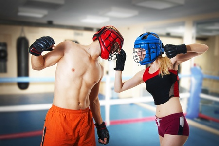 Couple workout on ring. Man and woman fighters in sports helmets. girl holds guy for helmet and is ready to punch in glove. Martial art - Kikboxing, muay thai, taekwondo, Jiu-jitsu, kungfu or mma. Stock Photo