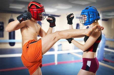 Couple workout on ring. Man and woman fighters in sports helmets. Guy kicking girl in head by leg and she is in protection. Kickboxig; muay thai; taekwondo; Jiu-jitsu or mma. photo