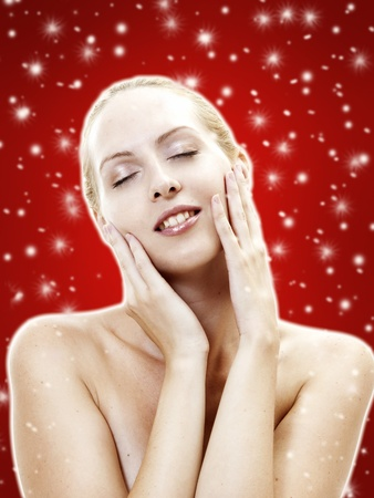 Nice lady with ideal skin. Female face - skincare as present on christmas. Spa salon, clean, cosmeticks. White snowflakes on red background photo