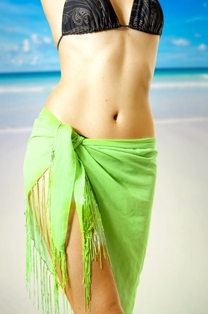 Young beautiful sexy tanned woman in bikini on sea beach. Fine female body. Summer diet. Close up photo