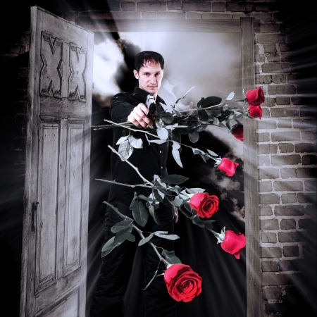 Man killer with seven red roses. He is on the threshold and points gun to the shot dropping roses, opened door, night Stock Photo