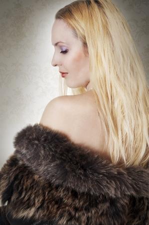 Fashion portrait of model woman. Rich blonde lady in fur coat back photo