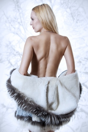 Sexy blonde woman in white fur coat with nude back in studio. Fashion portrait photo