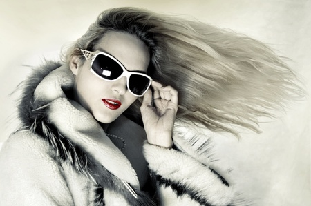 Fashion portrait of stunningly luxurious woman with long hair developing on wind and designer sunglasses photo