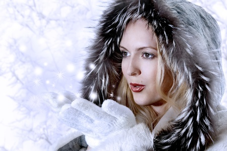 Fashion Woman with perfect skin Blowing Snow on blue background. She in white fur coat and  photo