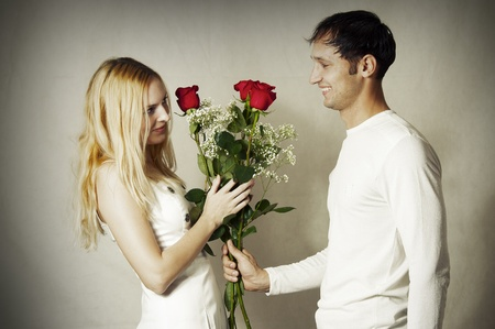 Young loving couple with flowers. Man gives his girlfriend red roses in honor of Valentines Day  photo