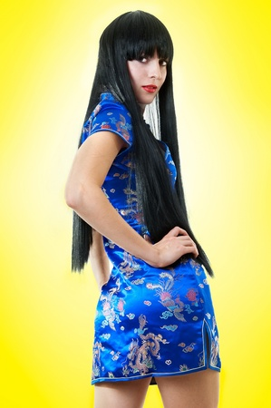 very: Beautiful slim stylish European brunette woman with very long black hair in Chinese dress