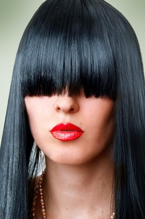 Closeup portrait of beautiful fashion woman with seductive red lips and creative black hairstyle with bang covering her eyes Stock Photo - 8723130