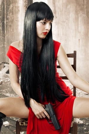 gun room: Sexy brunette woman in red dress with weapon (handgun) in hand sits on chair in old grunge decayed room