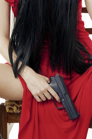 Big black gun in womans hand closeup. dangerous Girl in red dress photo