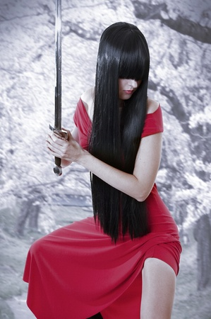 dangerous sexual mystery asian girl. Anime style woman with long black hair with sword and red seductive dress photo