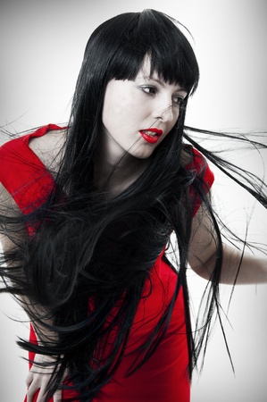 Fashion portrait of fresh and beautiful young brunet woman with red evening dress and hair developing on a wind. Flying healthy long black hair photo