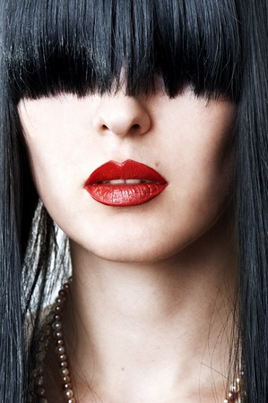 closeup fashion portrait of glamour woman face with red lips and creative black hairstyle with bang covering her eyes
