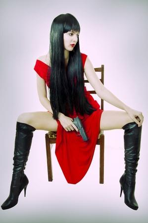 mujer con pistola: Morena de moda sexy mujer con pistola y cabello saludable. Ella sentado en una silla vieja en estudio en vestido rojo seductora y botas negras durante mucho tiempo ajustar las piernas