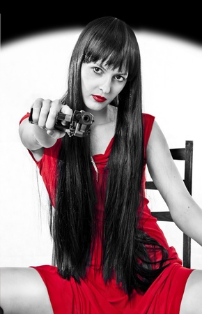 Portrait of sitting on a chair dangerous girl with handgun (black, white and red) and long hair in seductive red dress photo