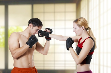 Couple fight. Young adult cute woman fighter punching man, studio shot photo