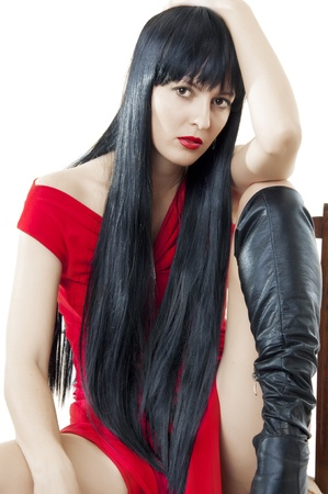 woman with luxuriant healthy long black hair in red dress and high boots sitting on a chair photo