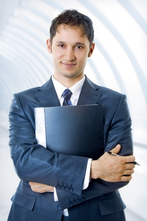 A young, successful handsome business man with pen and notebook smiling at office building in a light and mordern business hall.  photo