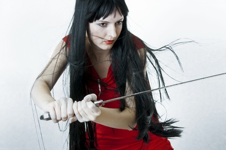 Sexual woman fighter with flying hair holds medieval sword photo