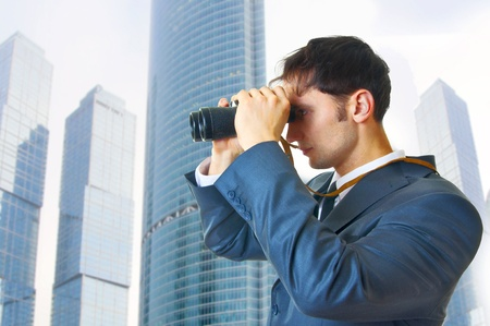 young adult business man with binoculars looking to the future outdoor photo
