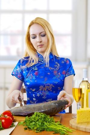 pez carpa: Mujer de j�venes adultos lindo estilo asi�tico est� cocinando un pescado fresco en blanco cocina en casa