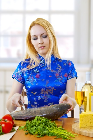 Young adult cute asian style woman is cooking a fresh fish in white kitchen at home photo