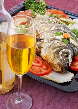 fried fish with fresh vegetables - herbs, tomatoes, lemon and salad. And white wine in bottle and glass. Served in the restaurant photo