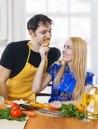 saxy: Love. Portrait of happy couple preparing food in light kitchen.