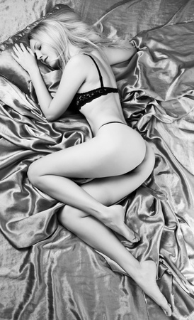 Seductive young woman with perfect saxy fit body and buttocks in lingerie sleeping on silk bed black and white Stock Photo - 9064647