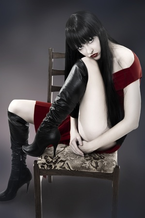 Fashion. Photo of beautiful woman with long black hair sitting on old chair on dark background