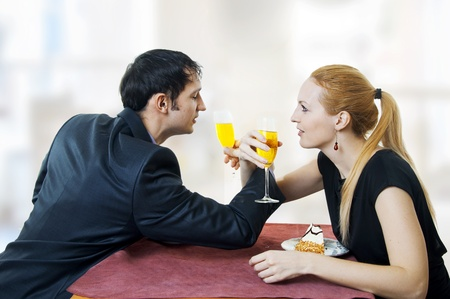 Young elegant happy amorous couple celebrating with white wine at restaurant. They are drinking photo