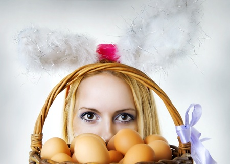 Beautiful easter bunny female looking over basket with eggs Stock Photo - 9117057