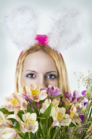 Beautiful easter bunny female looking over bunch of bright spring flowers photo